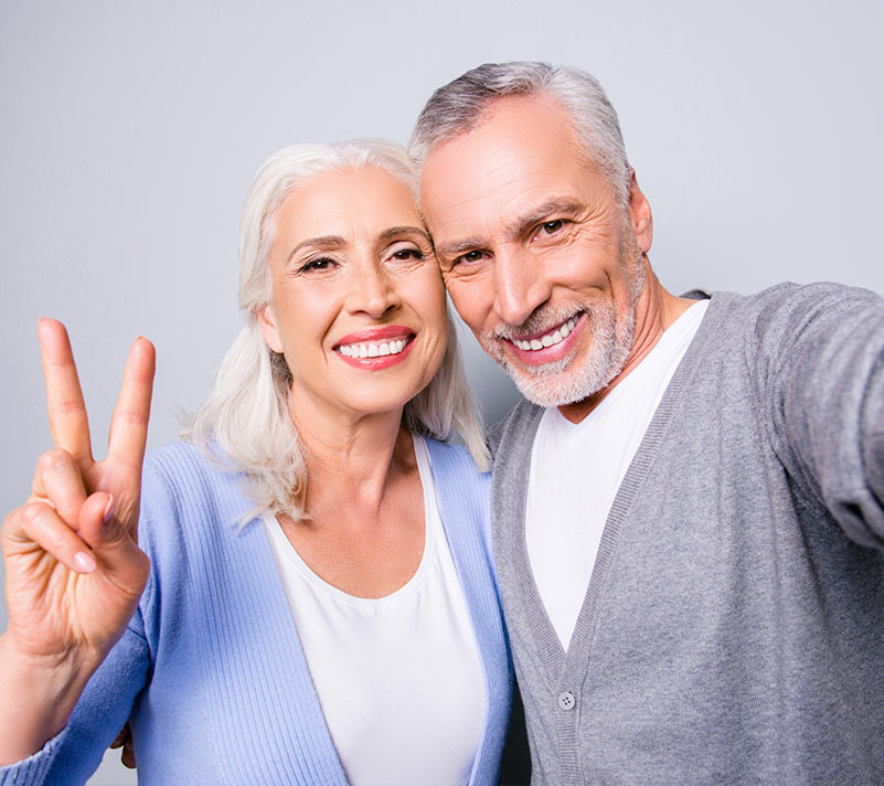smiling old couple and showing victory sign