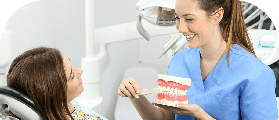 Hygienist Showing Patient How to Brush teeth